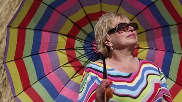Blondine mit Sonnenbrille und Regenschirm