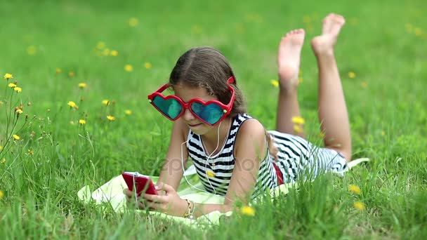 Girl with red smartphone lies on grass