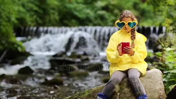 Mädchen mit rotem Smartphone sitzt in Flussnähe
