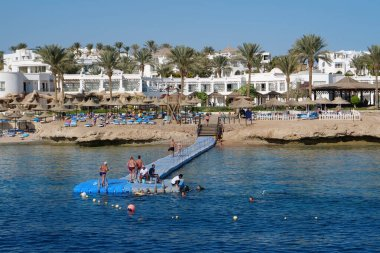 SHARM EL SHEIKH, EGYPT, SINAI, RED SEA, DECEMBER 7, 2019: People swims in Red Sea near coast of Sharm El Sheikh city in Egypt