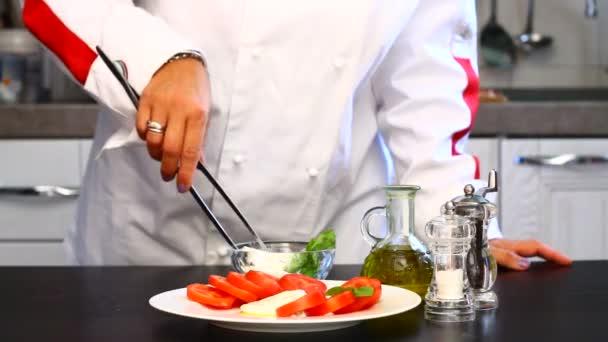 Profi szakács készít egy tányér, friss paradicsommal és mozzarellával