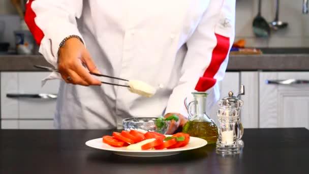 professionelle Köchin bereitet einen Teller mit frischen Tomaten und Mozzarella zu