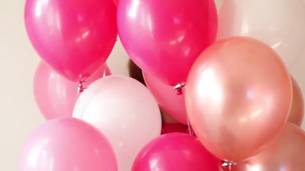mladá dívka hraje s růžovým vzduchem balón