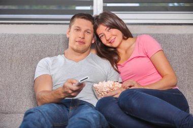 Photo of young couple eating popcorn and watching stock vector