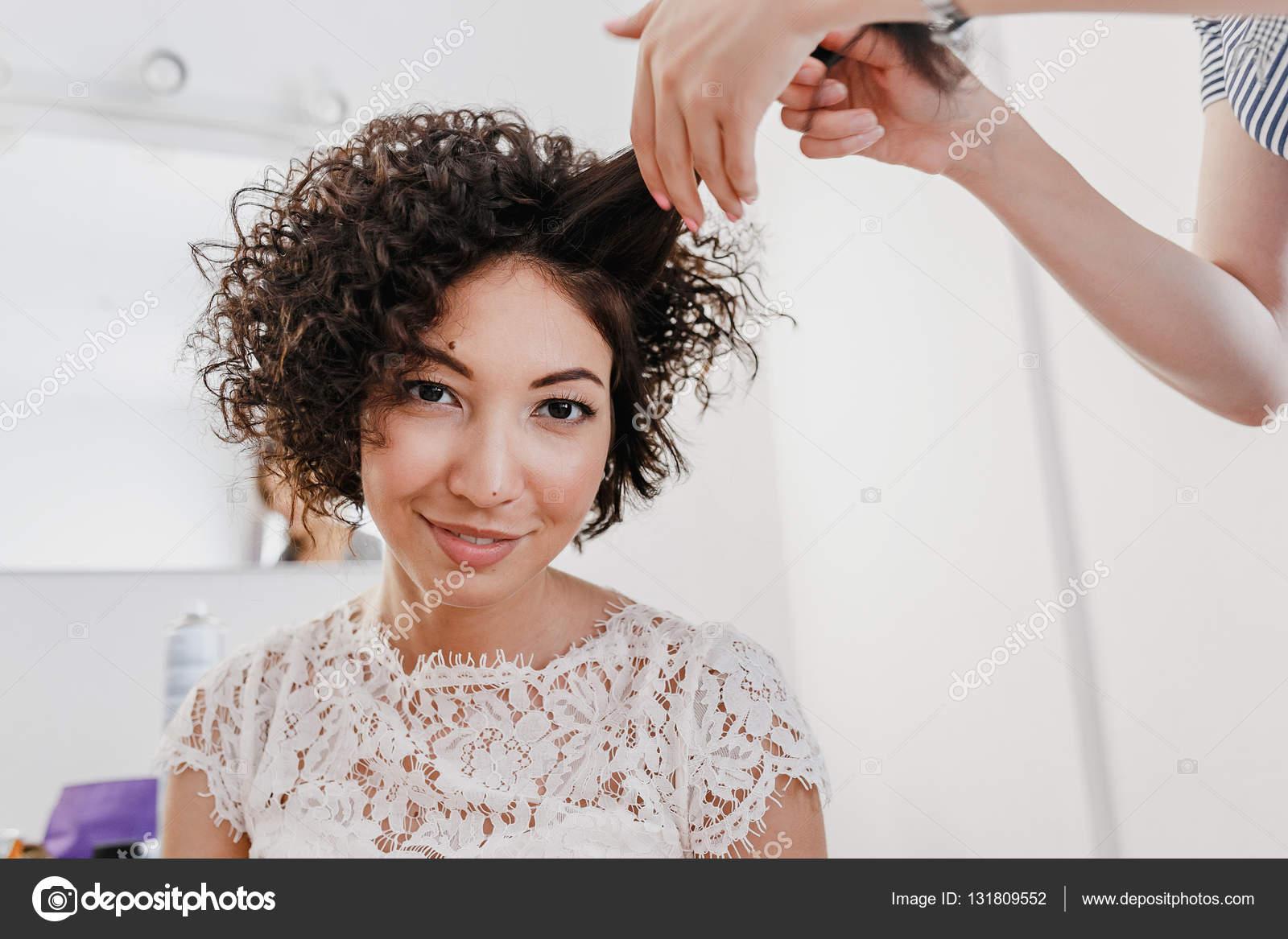 Professional hairdresser artist making curly hairstyle to charming ...