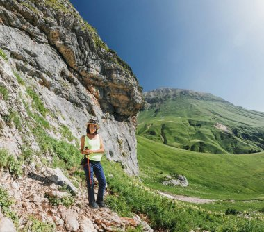 Young woman hiker walking in the path on the mountain edge. The concept of adventure and outdoor activities