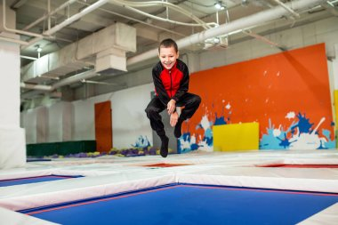 Boy is jumping high in striped tights on the big trampoline in kid sport center