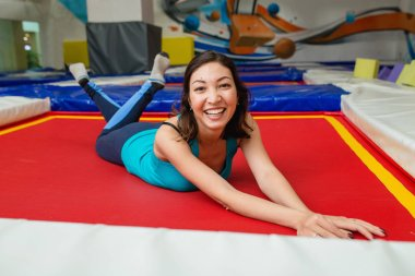 Young woman jumps on trampoline and resting in sports gym