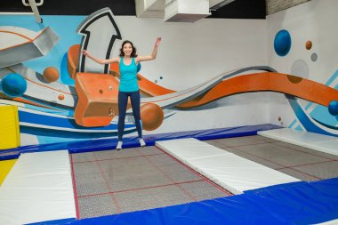 Jumping young woman in trampoline sport center indoors