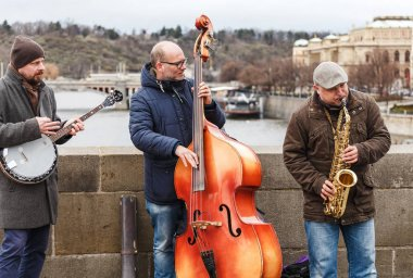 PRAGUE, CZECH REPUBLIC - 18 MARCH, 2017: Street band musicians play the cello, saxophone and banjo on the Charles Bridge in the center of Prague