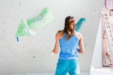 A sport woman climber on a climbing wall is exploring the route in an excellent athletic form with the relief muscles of the arms and shoulders