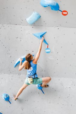 MAY 2017, UFA, RUSSIA, FINAL IN CLIMBING CHAMPIONSHIP: A woman climbs on an artificial open rock wall in the All-Russian competitions in the category of difficulty and bouldering