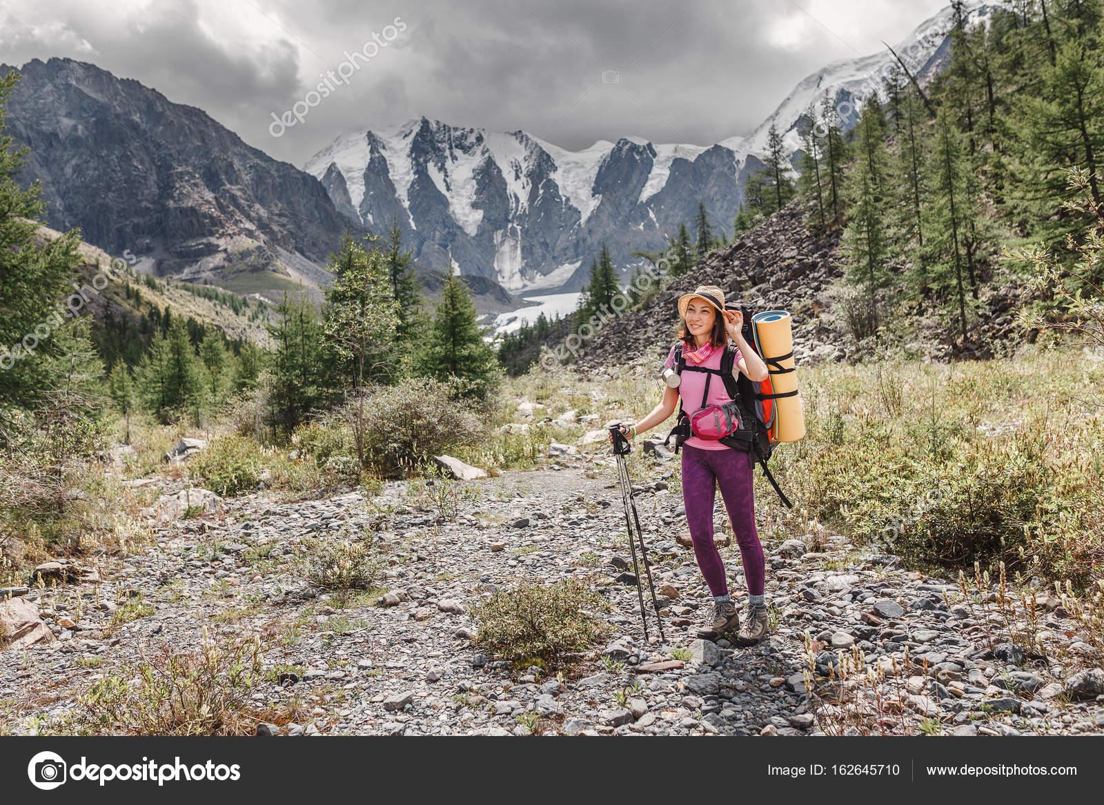 En kvinna med ryggsäck reser längs floddalen i bergen. Vandring och  trekking koncept– stockbild 0ce13ed6bcda8