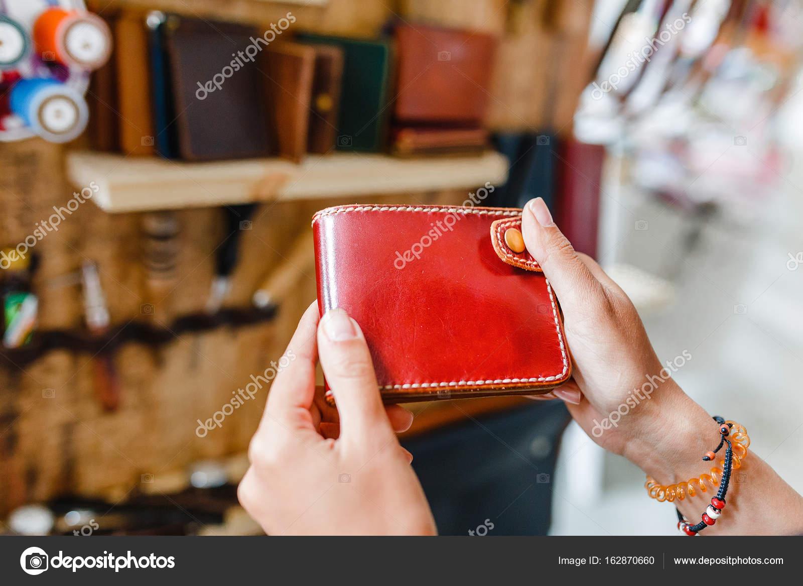 6458fe6b7 Mãos femininas do cliente tentar mão fez carteira de couro trabalhada no  fundo de uma loja