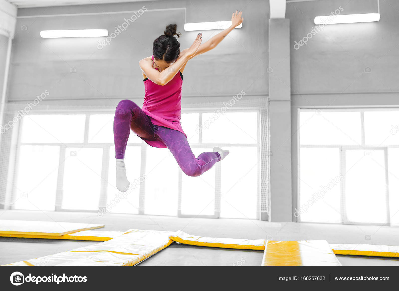 Modern hip-hop woman dancer jumping and doing dab in trampoline