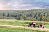 Člověk zemědělec jezdí na starý traktor v obci