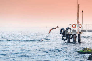 ISTANBUL, TURKEY - SEPTEMBER 10, 2017:  Group of friends jumping off the pier into the Black sea in Istanbul