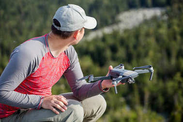 A man launches a modern intelligent quarter copter drone during a hike through the forest