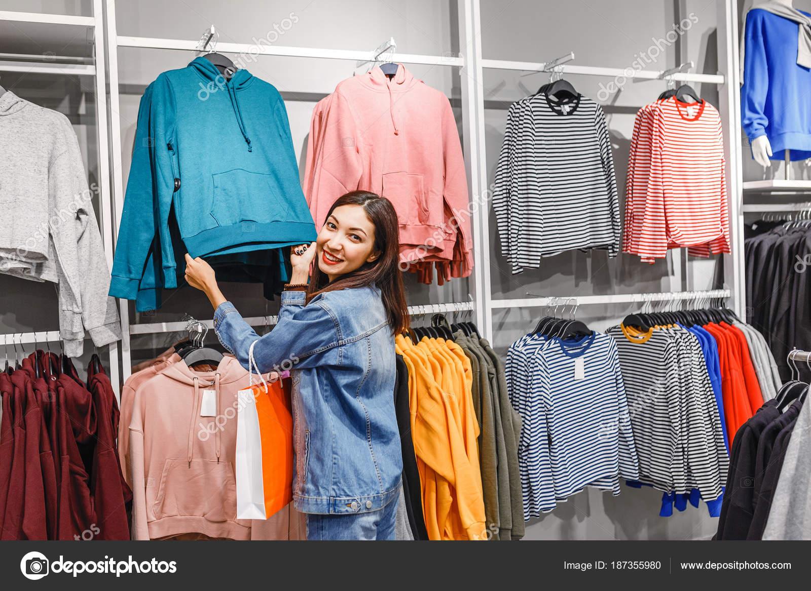 b5f5ec956 Mulher escolher roupas de moda na loja de varejo no centro comercial da  cidade