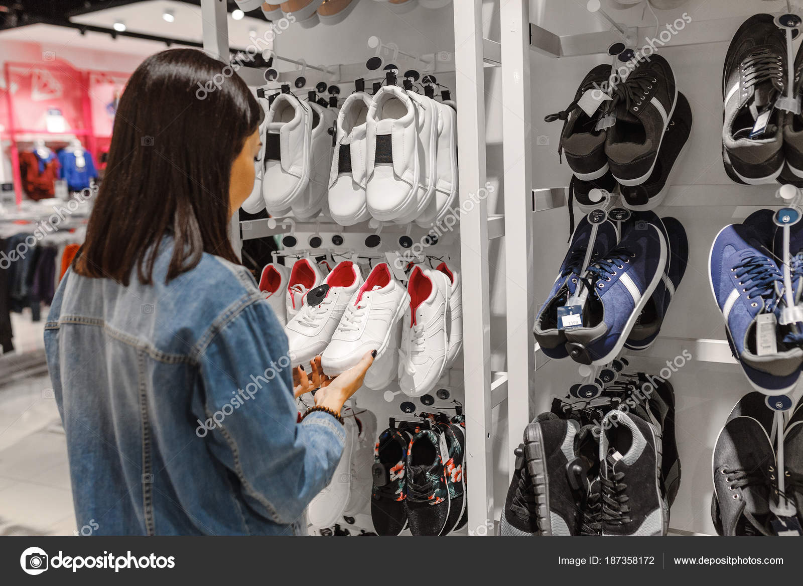 Cliente joven feliz elegir el par de zapatillas de deporte zapatos y compra  en tienda de ropa 8b2f6ad867551