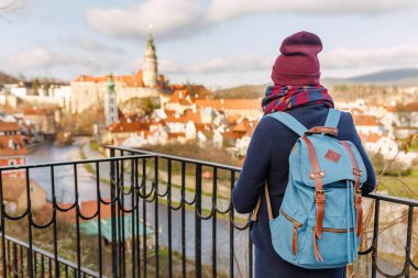 Woman tourist in a coat with a backpack travels at the old streets of Cesky Krumlov city, Europe vacation concept