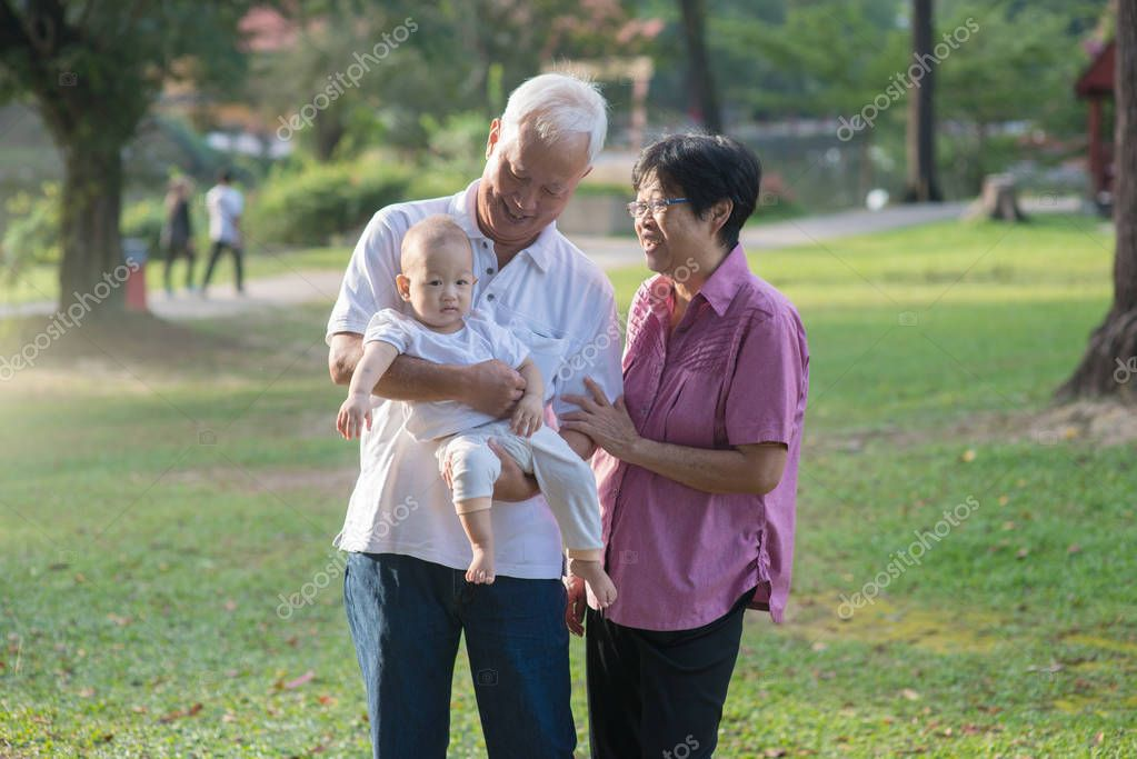 Chinese Grandparents holding Granddaughter