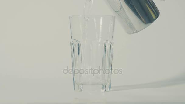 Nalévání vody do sklenice z hrnce