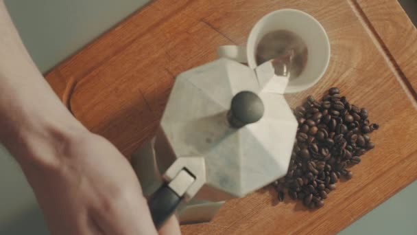 Pouring coffe into white cup from the coffee geyser