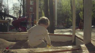 A kid playing in a sandbox