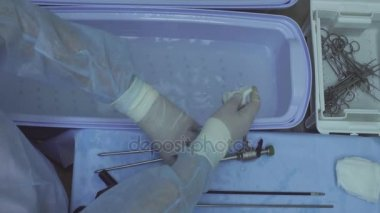 The surgical nurse washing medical instrument