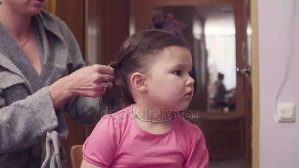 Young woman is combing girls hair