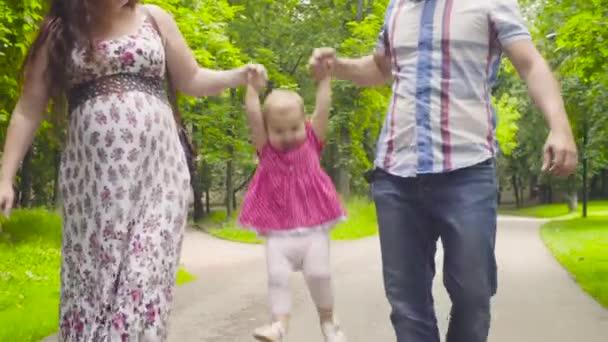 Boldog szülők a baba lány séta egy parkban