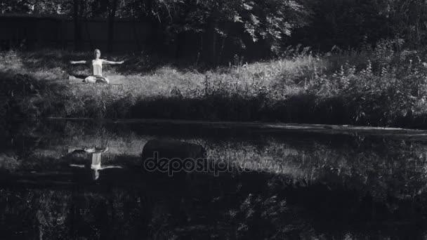 Mladá žena jógu ásany na břehu řeky