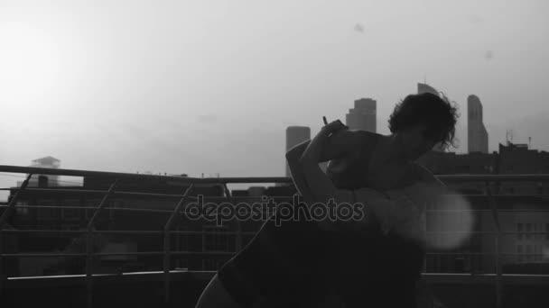 Siluety mladý pár tančí na západ slunce