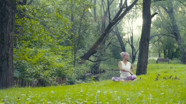 Žena, která dělá cvičení jógy u řeky