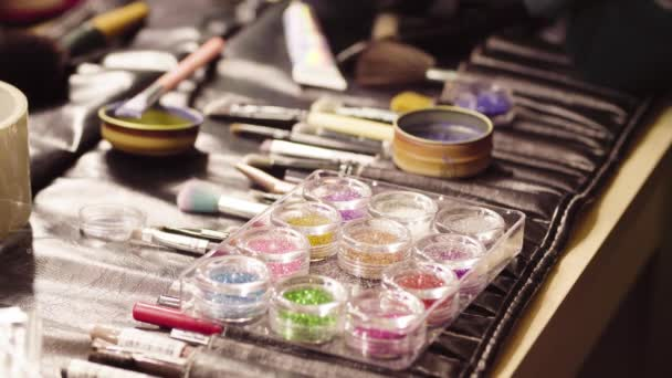 Sklenice s lesklou pudr a make-up štětce