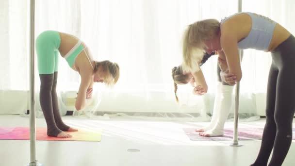 Three women doing yoga exercises in studio.