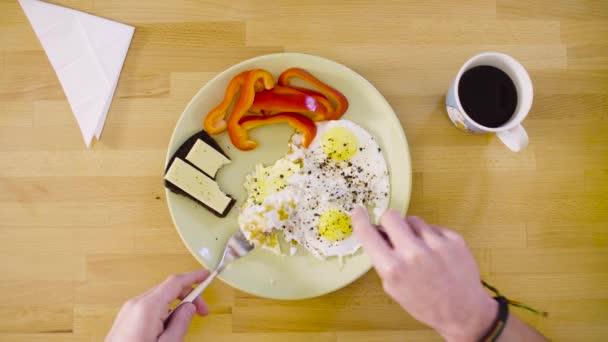 Člověk jíst omeletu a sendvič