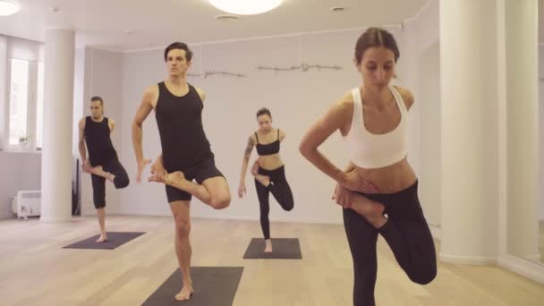 Yoga class. People practicing yoga in the studio