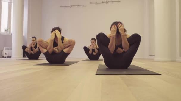 Yoga class. Ashtanga yoga. Garbha pindasana.