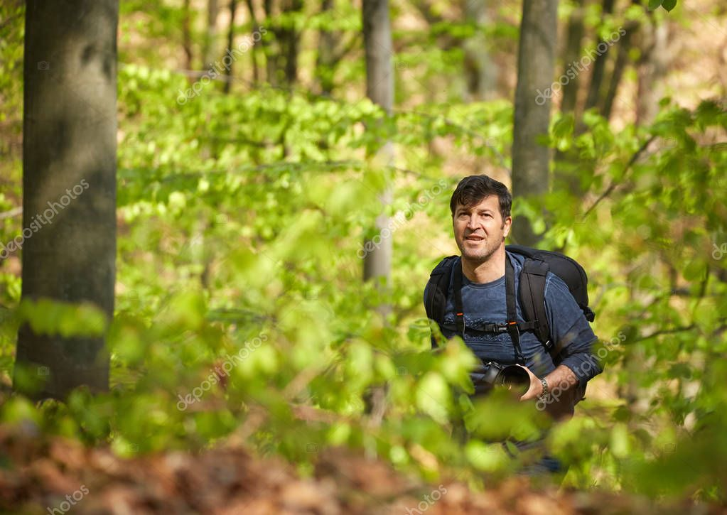 Tourist with backpack in forest