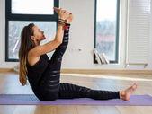 Fotografia Insegnante di yoga della giovane donna nel suo studio prendendo varie pose dalla finestra