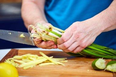 Man chopping spring onions on a wooden board, closeup shot