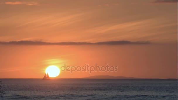 Loď plující na pobřeží pláže v golden sunset