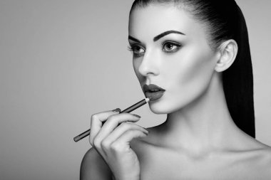 Black and white photo of woman painting lipstick