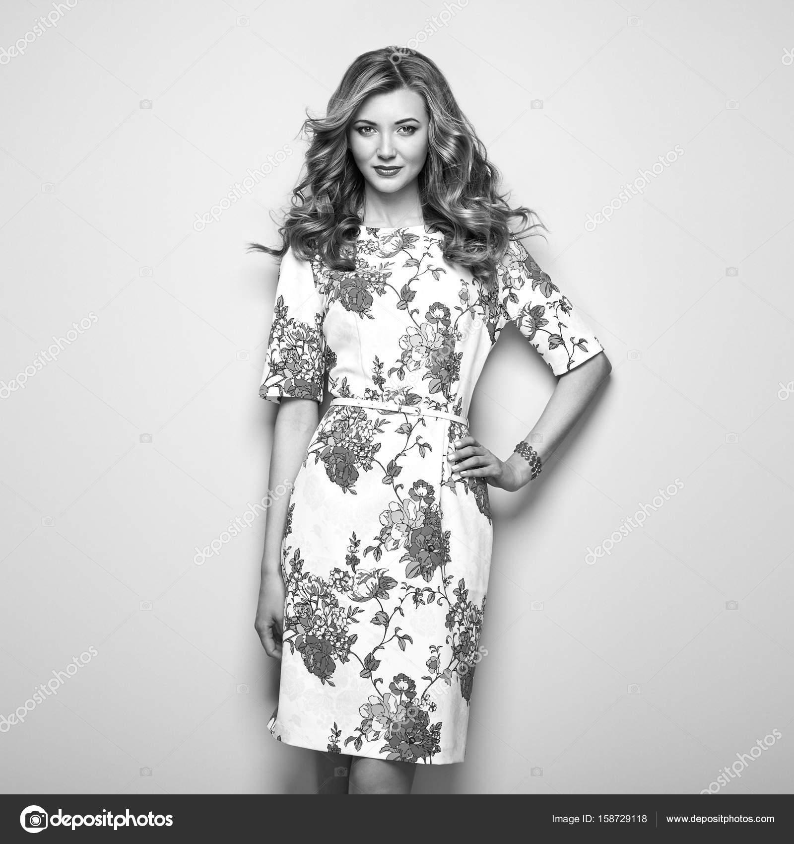 14a49bacb5 Szőke fiatal nő virágos nyári ruha. Lány pózol a fehér háttér előtt. Elegáns  hullámos frizura. Divat fekete-fehér fotó. Szőke hölgy — Fotó szerzőtől ...