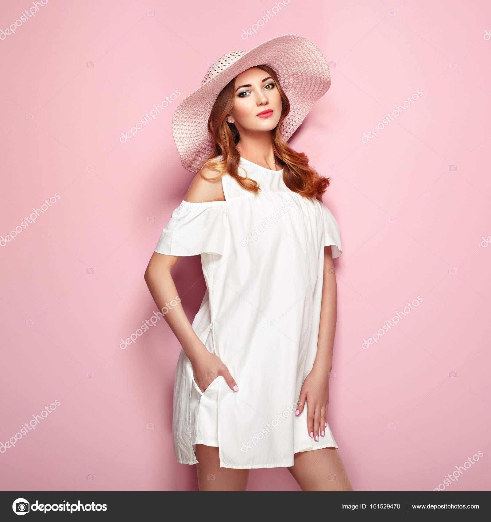 c053c6b822f0 Giovane donna bionda in abito estivo bianco e cappello di estate. Ragazza  in posa su uno sfondo rosa. Gioielli e abbigliamento.