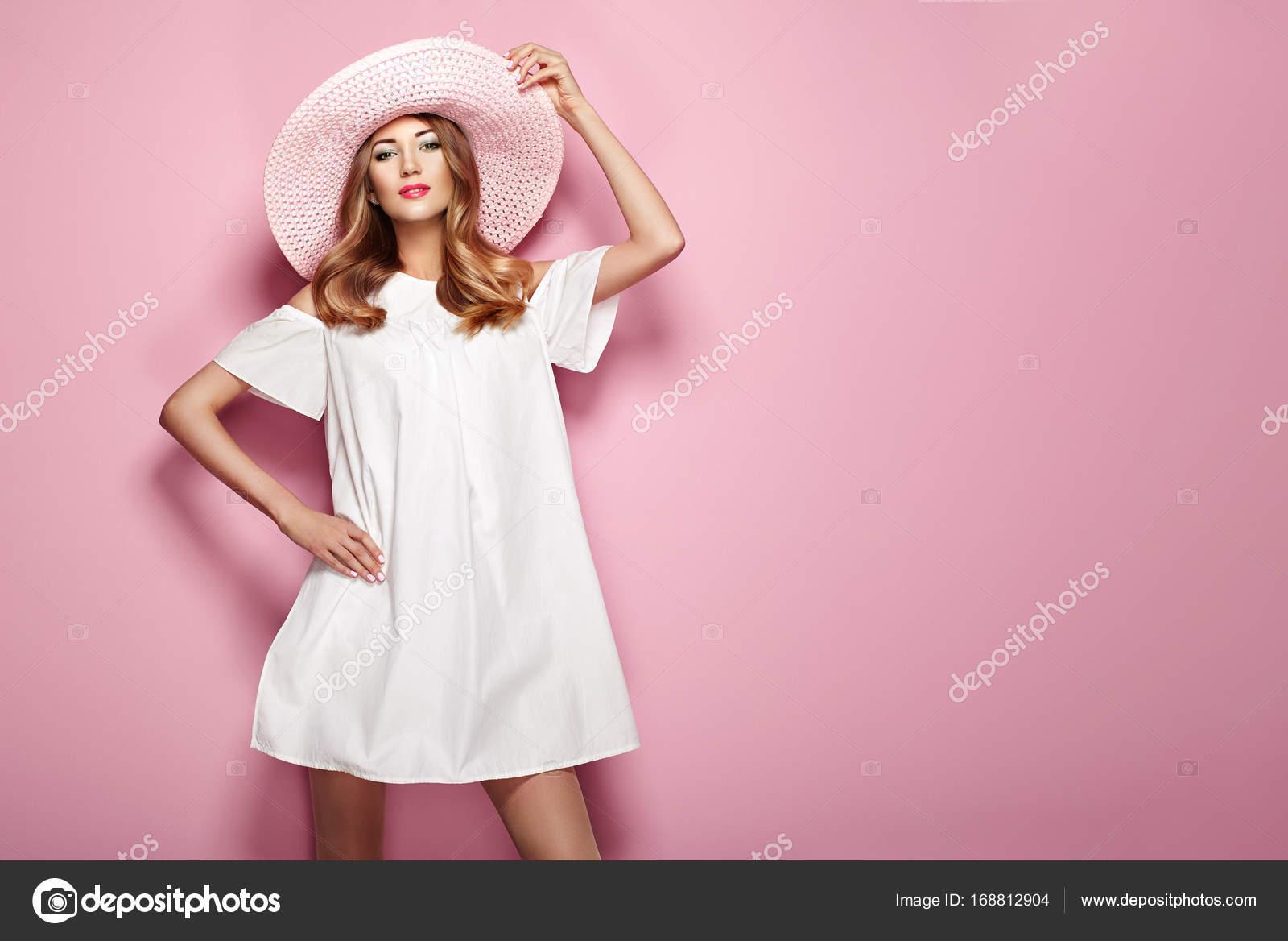 11a02b54f77f Giovane donna bionda in vestito bianco elegante e cappello di estate.  Ragazza in posa su uno sfondo rosa. Gioielli e abbigliamento.