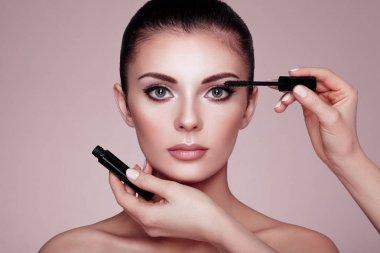 Beautiful brunette woman paints the eyelashes