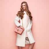 Mladá žena v bílém podzimním kabátě